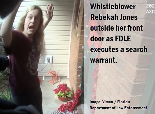 Florida Whistleblower outside her front door with hands up.